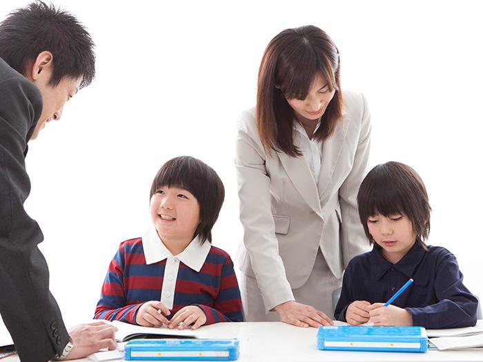 勉強中の子どもと教える先生