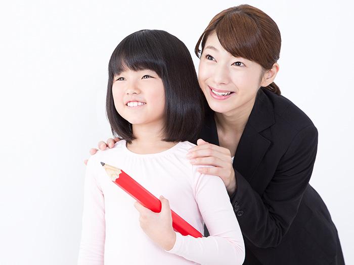 女の子の肩に手を置く女性