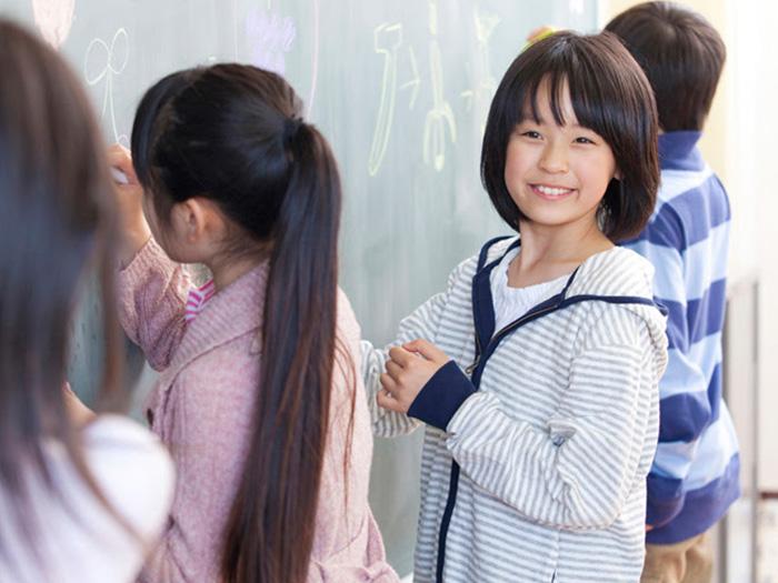 黒板に絵を描く児童
