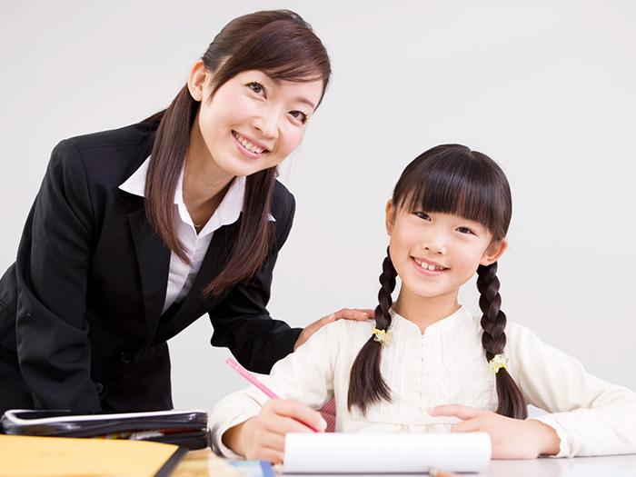 勉強中のおさげの女の子と先生